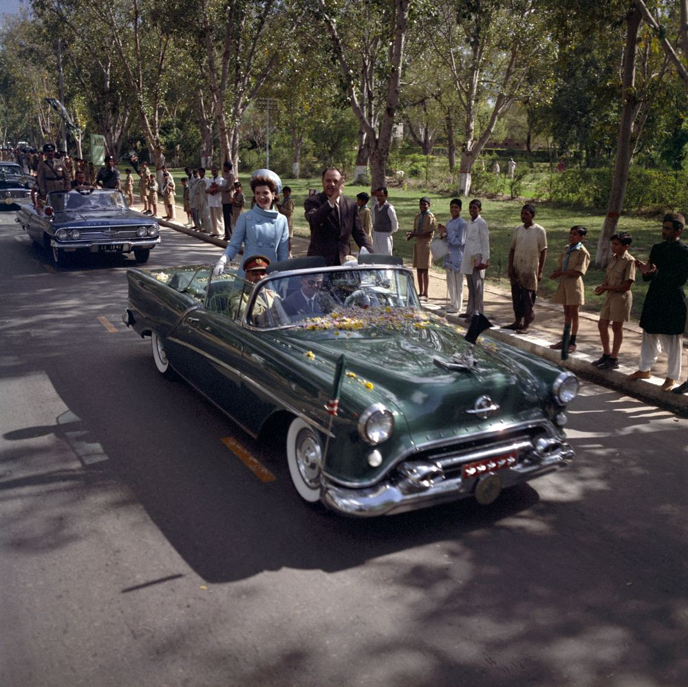 First Lady Jacqueline Kennedy and President of Pakistan, Mohammad Ayub Khan, travel by car to the residence of the Governor of West Pakistan, Malik Amir Mohammad Khan, following Mrs. Kennedy's arrival in Lahore, Punjab, Pakistan. Secret Service agent, James Jeffries, sits in middle of front seat of car.