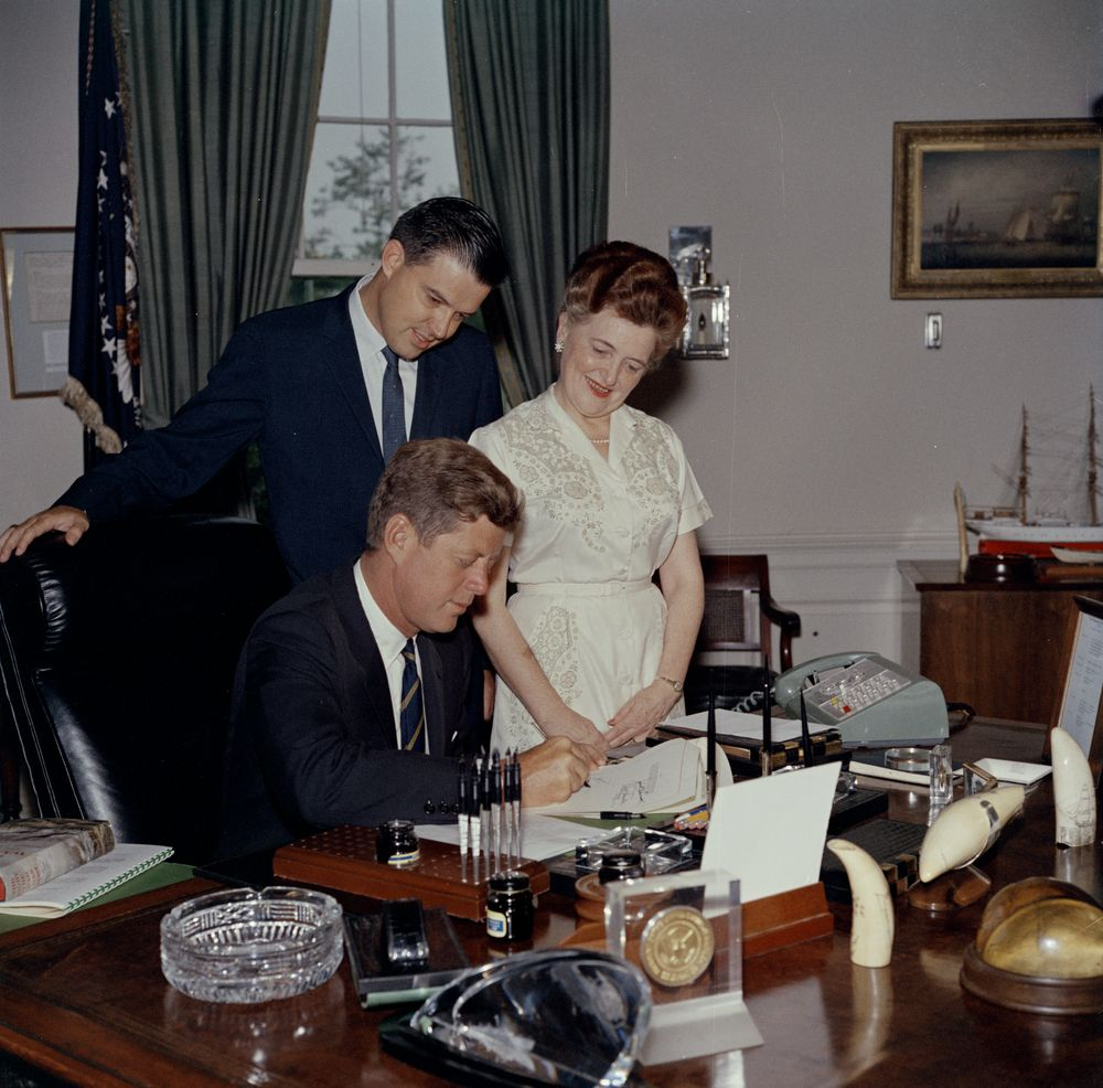 President John F. Kennedy (seated at desk) signs a bill to authorize the Mann Creek Federal Reclamation Project in Idaho. Looking on (L-R): Senator Frank Church and Representative Gracie Bowers Pfost, both of Idaho. Oval Office, White House, Washington, D.C.