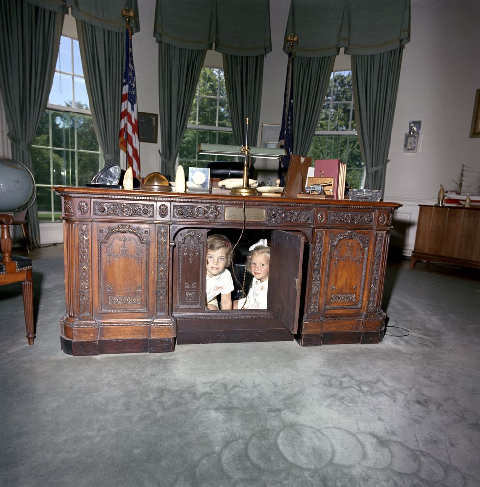 Caroline Kennedy And Cousin Kerry Sit Under Desk In Oval Office