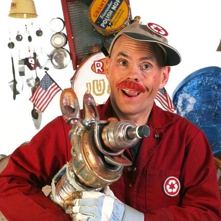 Image of Rick Adams dressed in a red jumpsuit and hat with recycling buttons on them holding a dog made out of recycled metal.