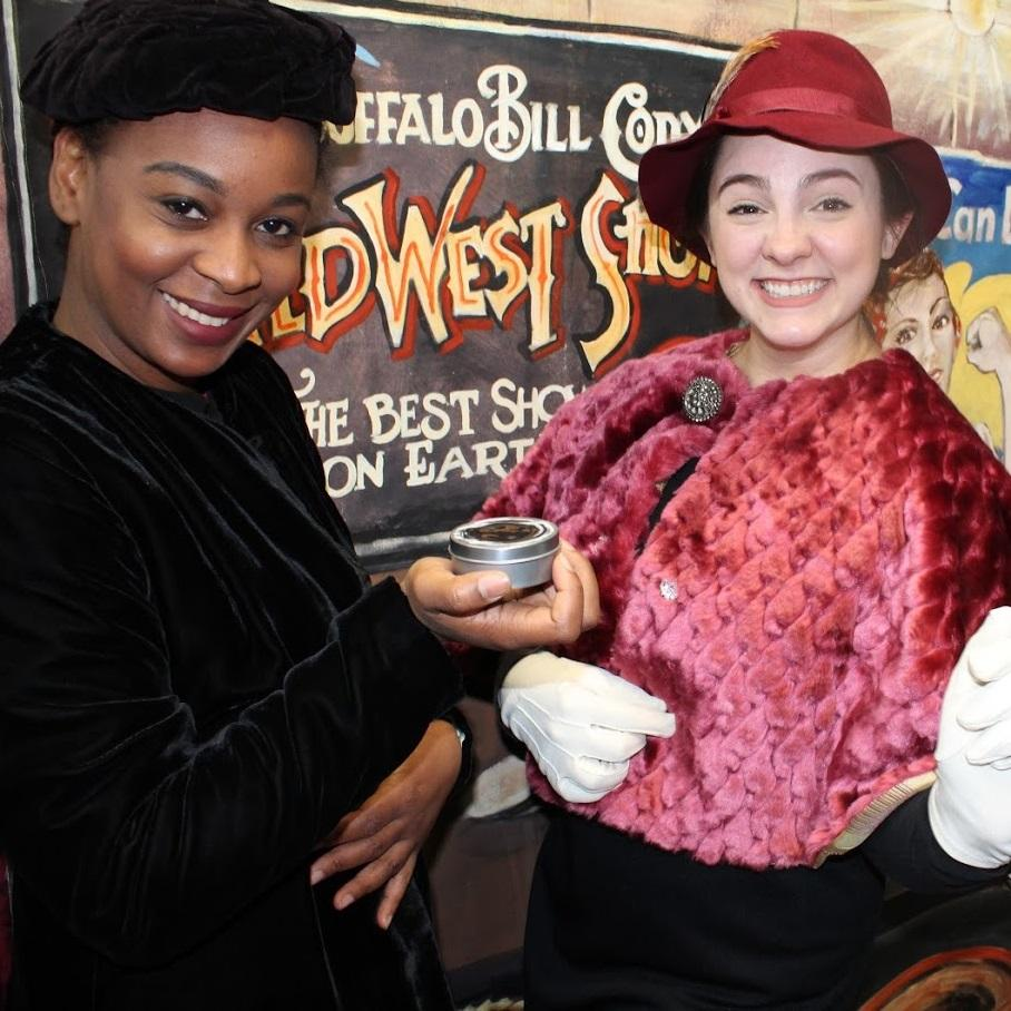 Image of two women in from of a couple of historical posters, the African American women on the left is wearing a black velvet dress and matching hat and the white woman on the right is wearing a red hat with matching shawl and white gloves.