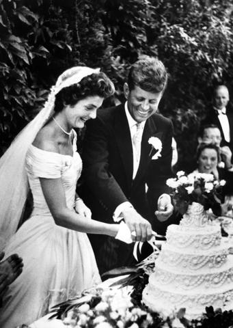 John and Jacqueline Kennedy cut cake at their wedding.