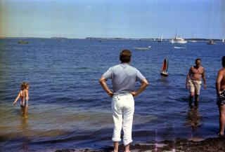 President John F. Kennedy (center, back turned) watches the launch of John F. Kennedy, Jr.'s toy sailboat in Hyannis Port