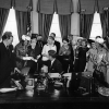 President John F. Kennedy distributes pens after signing the Equal Pay Act in the Oval Office of the White House, Washington, D.C.